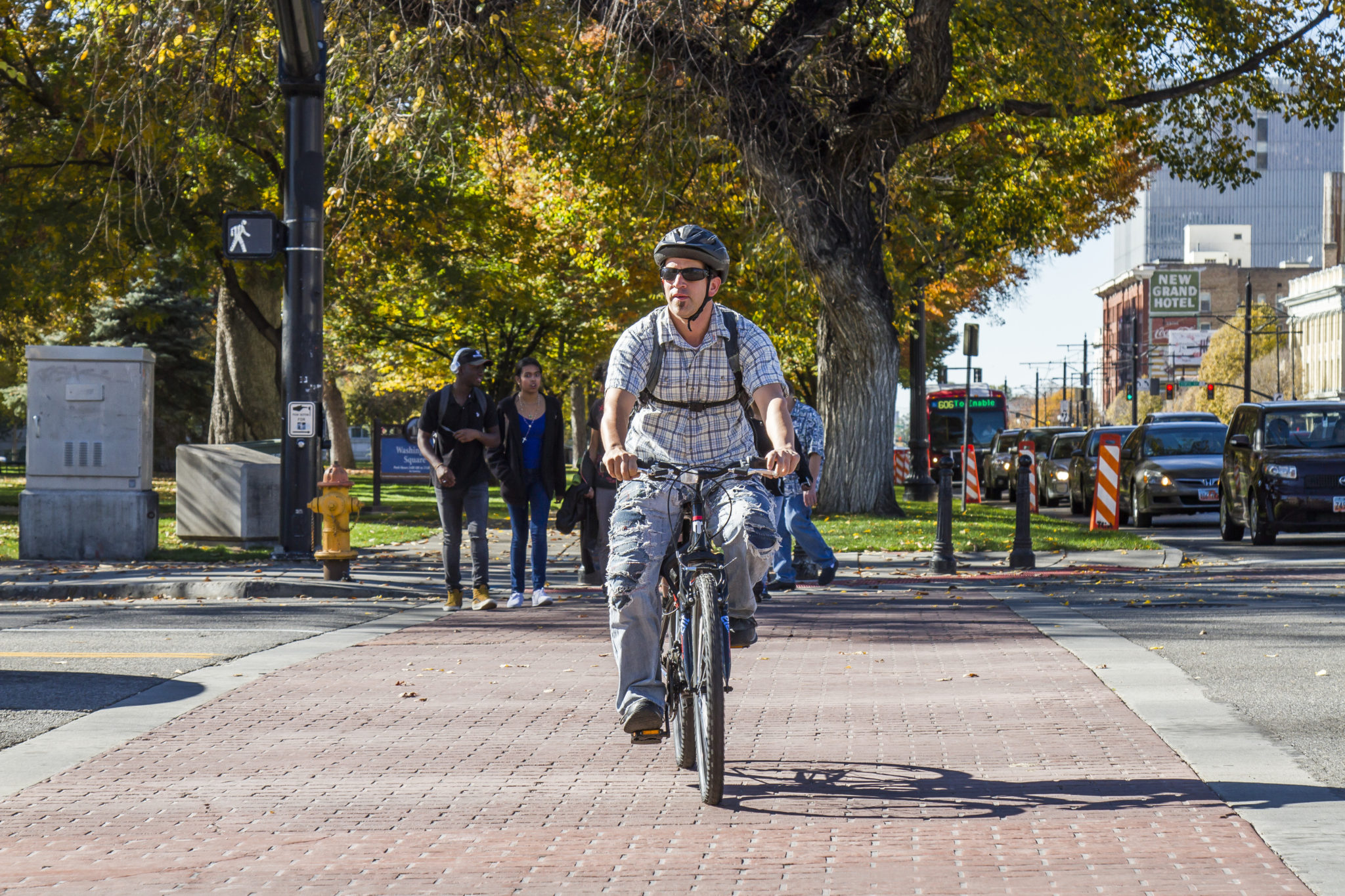 Bicyclist And Pedestrians Utilize Crosswalk In Salt Lake City.