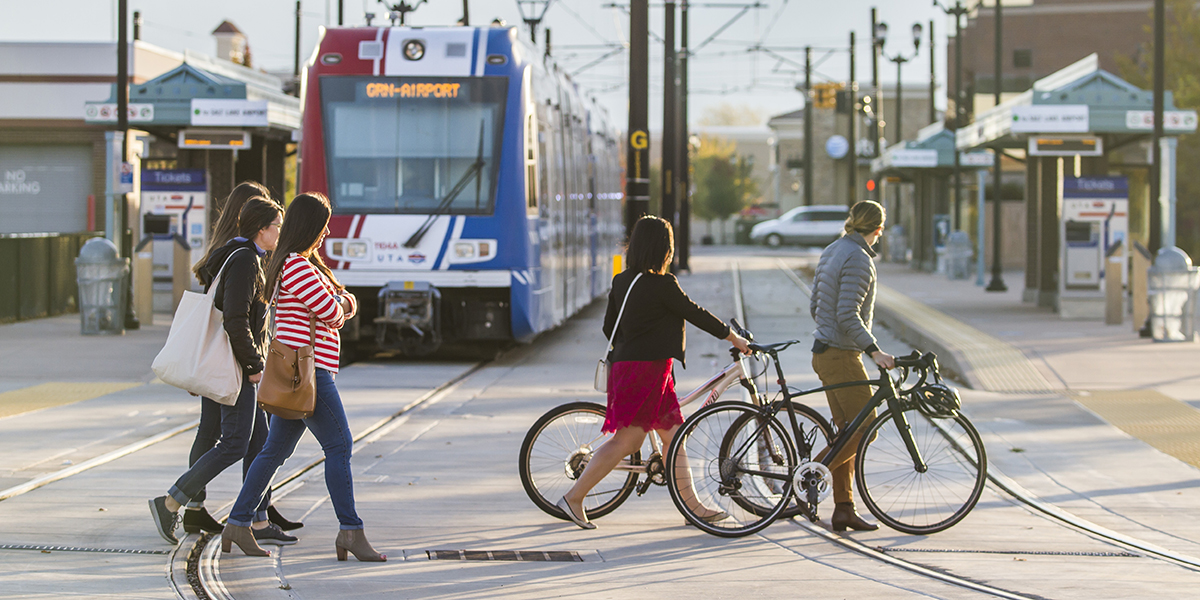 Pedestrians And Bicyclists Cross The TRAX Rails In West Valley City.