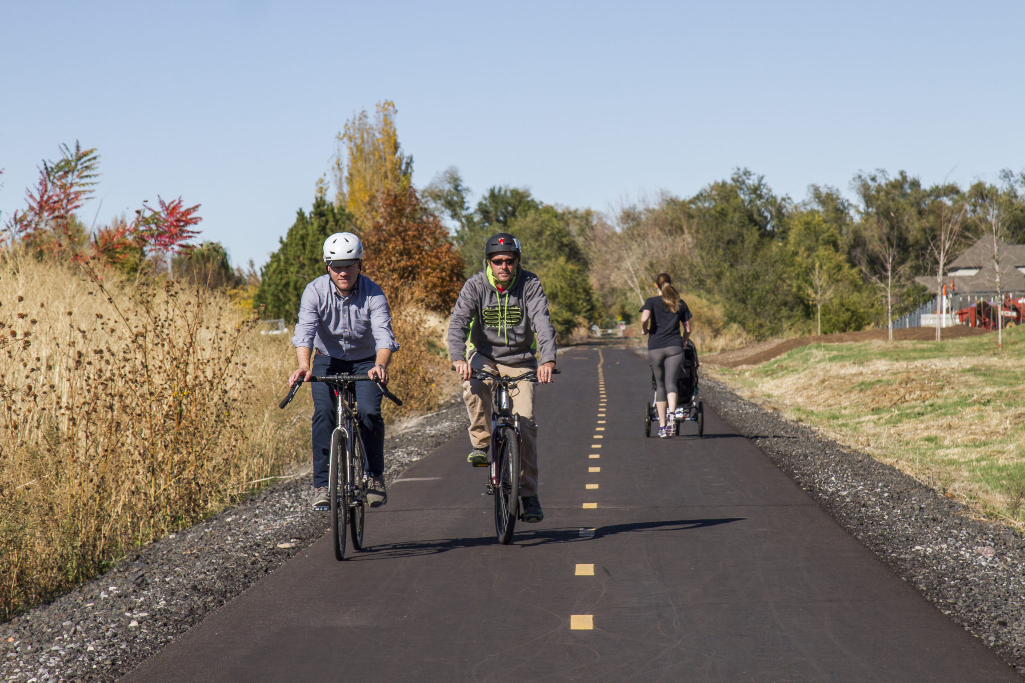 Bicyclists And A Jogger With A Stroller Utilize The Golden Spoke Trail Network.