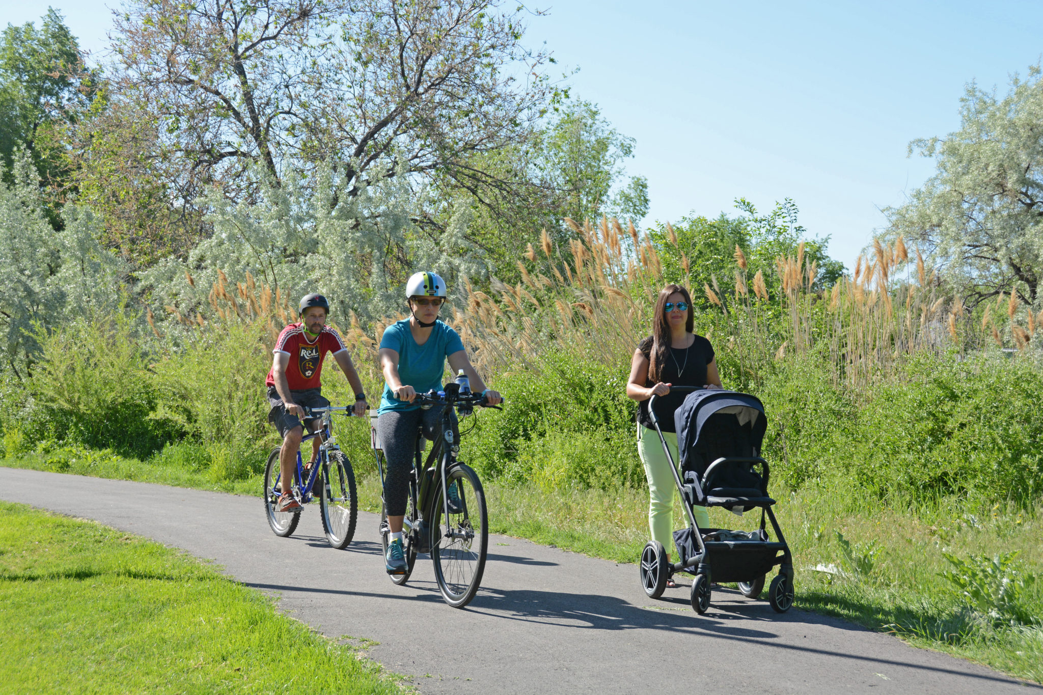 Bicyclists And A Walker With A Stroller Utilize The Golden Spoke Trail Network (Jordan River Trail).