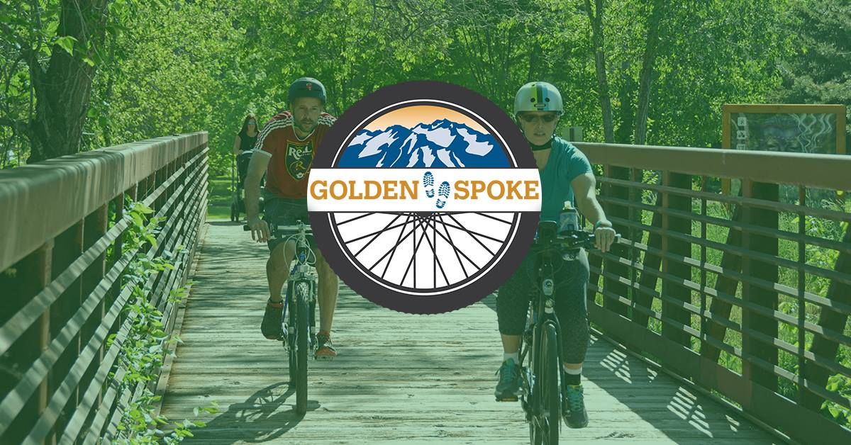 Image of two bicyclists riding over a Jordan River Parkway bridge in the background and Golden Spoke logo in the foreground.